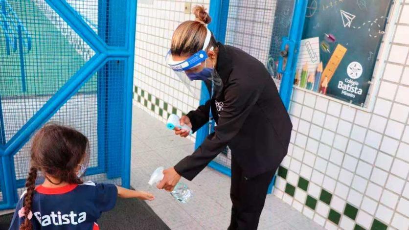Criança higieniza as mãos com álcool em gel antes de entrar na sala de aula Foto Foto: Gilson de Souza